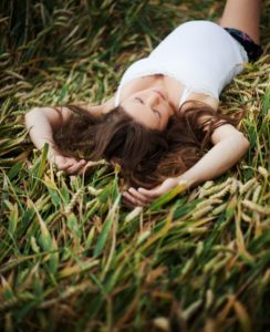 Lady laying in the grass practicing Dialectical Behavior Therapy